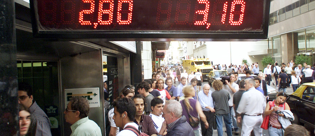 Hundreds of Argentines line up outside exchange houses in Buenos Aires'financial district to buy dollars as the peso dropped to record lows,March 22, 2002. Argentina's peso plummeted to record lows despite efforts by the Central Bank to prop up the local currency.REUTERS/Enrique MarcarianRR/SV - RP3DRHZFINAA