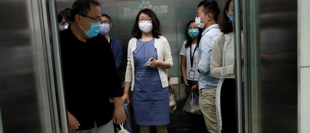 Empleados con máscaras faciales son vistos dentro de un ascensor en la sede de Baidu en Beijing, después del brote de la nueva enfermedad coronavirus (COVID-19), China 18 de mayo de 2020.