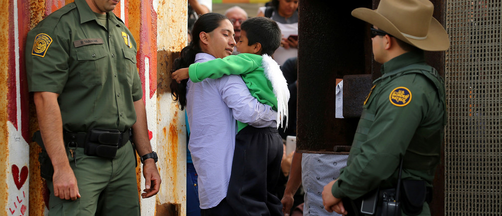 U.S. Border patrol agents stand at an open gate on the fence along the Mexico border to allow Luis Eduardo Hernandez-Bautista hug Ty'Jahnae Williams and his father Eduardo Hernandez (not in view), as part of Universal Children's Day at the Border Field State Park, California, U.S., November 19, 2016.  REUTERS/Mike Blake - RTSSFNN