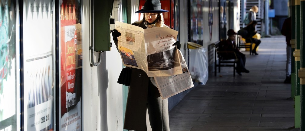 A woman reads a newspaper whilst waiting for a tube train on an autumn morning in London, Britain, October 30, 2017.