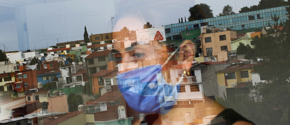Monica Samudio, 46, whose husband Jorge Garcia, 51, died from the coronavirus disease (COVID-19), is reflected in the window as she looks out of her new apartment, in Mexico City, Mexico April 29, 2020. Samudio said she moved from her previous home after feeling discriminated against when she and her husband contracted the disease. Picture taken April 29, 2020