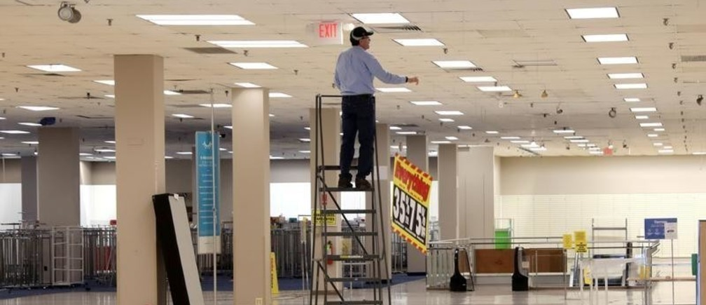 A worker removes sale banners inside a closed Sears department store one day after it closed as part of multiple store closures by Sears Holdings Corp in the United States in Nanuet, New York, U.S., January 7, 2019. REUTERS/Mike Segar - RC1828F34FF0