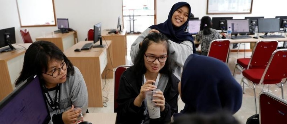 Volunteers share jokes during a break as they upload the details of vote tally forms, of this month's election, in a room at Joko Widodo's national campaign team office in Jakarta, Indonesia, April 29, 2019. Picture taken April 29, 2019. REUTERS/Willy Kurniawan - RC176BDA7F00