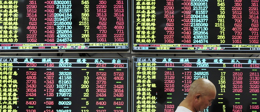 An investor looks at his mobile phone in front of electronic screens showing stock information at a brokerage house in Jiujiang, Jiangxi province, China, August 10, 2015. China stocks jumped more than 4 percent on Monday on possible restructuring among major shipping firms and in other key sectors, and on hopes that less volatile trading may soon convince fund managers to get off the sidelines and re-invest billions in cash