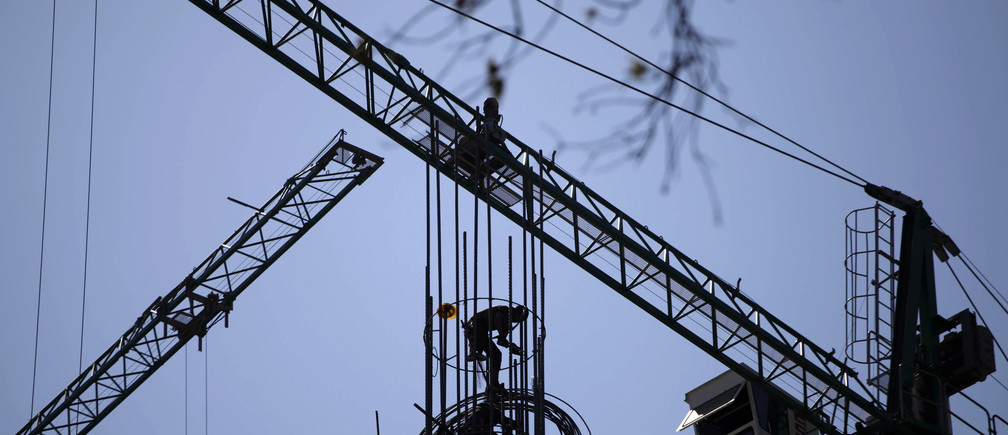 A worker stands on a structure at a construction site in Mexico City January 25, 2011.