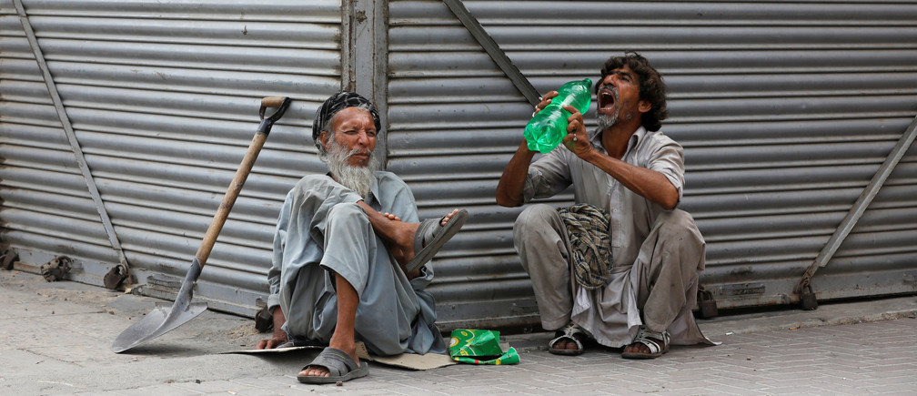 Daily wage laborers, wait for work as they sit outside closed shops, during lockdown amid the outbreak of coronavirus disease (COVID-19), at a market in Karachi, Pakistan April 14, 2020. REUTERS/Akhtar Soomro - RC2C4G9PM4NR