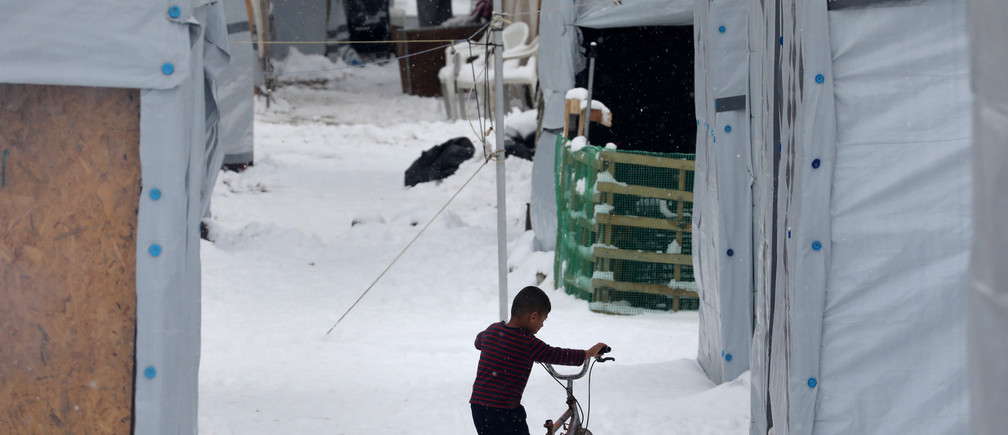 A stranded Syrian refugee child tries to move his bicycle during a snowstorm at a refugee camp north of Athens, Greece January 10, 2017.REUTERS/Yannis Behrakis - RTX2YBSF