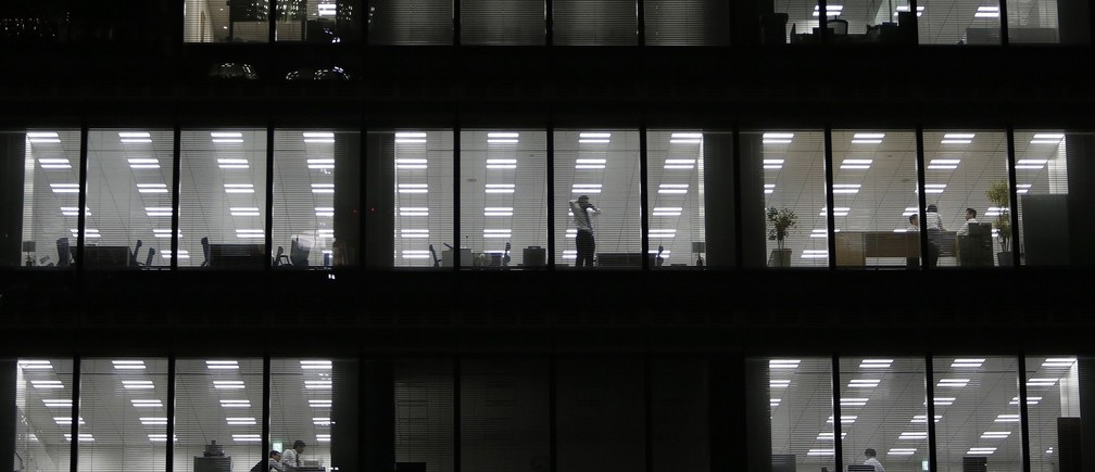 A man using his mobile phone stands near a glass window at a building at a Tokyo's business district March 18, 2015. Japanese blue-chip firms announced wage hikes that topped increases last year, but overall pay raises across corporate Japan are not expected to offset higher costs of living or be enough to drive a sustainable economic recovery. REUTERS/Yuya Shino