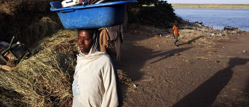 A woman carries a pail on her head after washing dishes in the Niger River in Gao February 20, 2013.