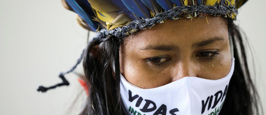 """Una mujer indígena, con una máscara facial que dice """"Las vidas de los indígenas importan"""", mira durante el funeral del Jefe Messias Kokama, de 53 años, del Parque das Tribos, que falleció debido a la enfermedad coronavirus (COVID-19), en el Parque das Tribos de Manaus, Brasil, el 14 de mayo de 2020."""
