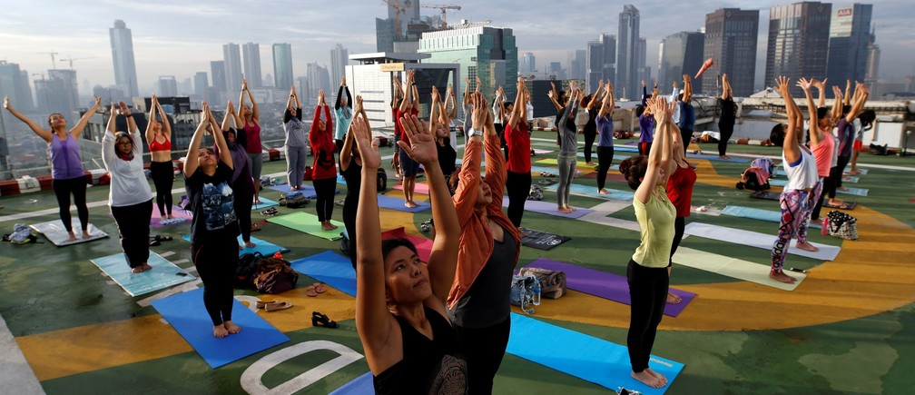 People take part in a sunrise yoga class on the helicopter landing pad on the roof of the Grand Sahid Jaya hotel in Jakarta, Indonesia September 25, 2016.