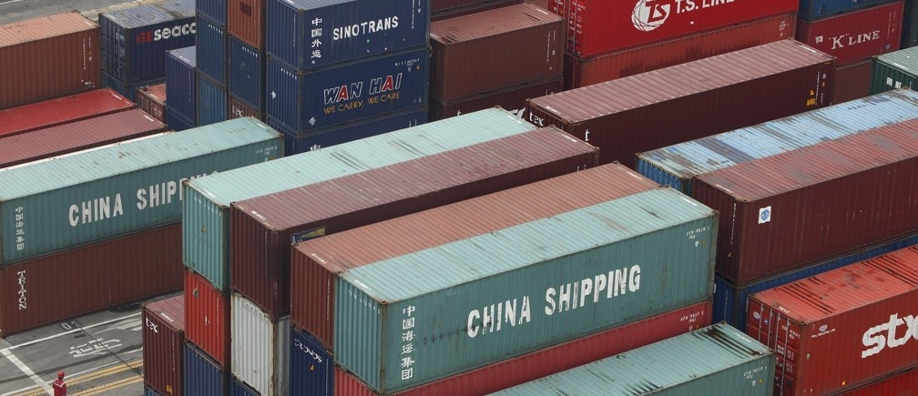 A worker walks in a shipping container area at the Port of Shanghai April 10, 2012. China returned to an export-led trade surplus of $5.35 billion in March, heralding the prospect that a rebound in the global economy is lifting overseas orders just in time to compensate for a slowdown in domestic demand.