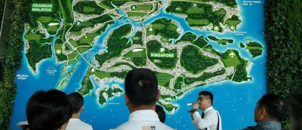 A sales agent talks about the proximity of Country Gardens' Forest City project to Singapore at their showroom in Johor Bahru, Malaysia February 21, 2017. Picture taken February 21, 2017. REUTERS/Edgar Su - RC1C79D331D0