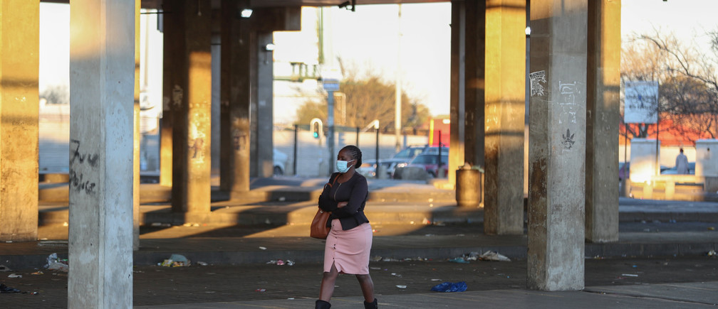 A Stranded commuter walks at a deserted Baragwanath taxi rank during a protest by the South African minibus taxi operators against the government's financial relief package to the taxi industry, during the coronavirus disease (COVID-19) lockdown, in Soweto, South Africa, June 22, 2020. REUTERS/Siphiwe Sibeko - RC2AEH9TH63Z
