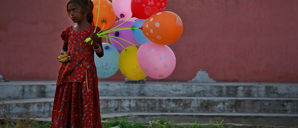 A young girl sells balloons by the Yamuna River as devotees carrying idols of the Hindu god Ganesh, the deity of prosperity, immerse the idol on the last day of the ten-day-long Ganesh Chaturthi festival in Delhi, India, September 15, 2016. REUTERS/Cathal McNaughton     TPX IMAGES OF THE DAY      - RTSNWSK