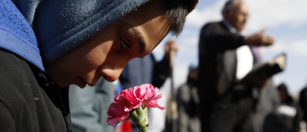 A boy holds a flower during the funeral of 16-year-old Karina Ivette Delgado in Ciudad Juarez February 3, 2011