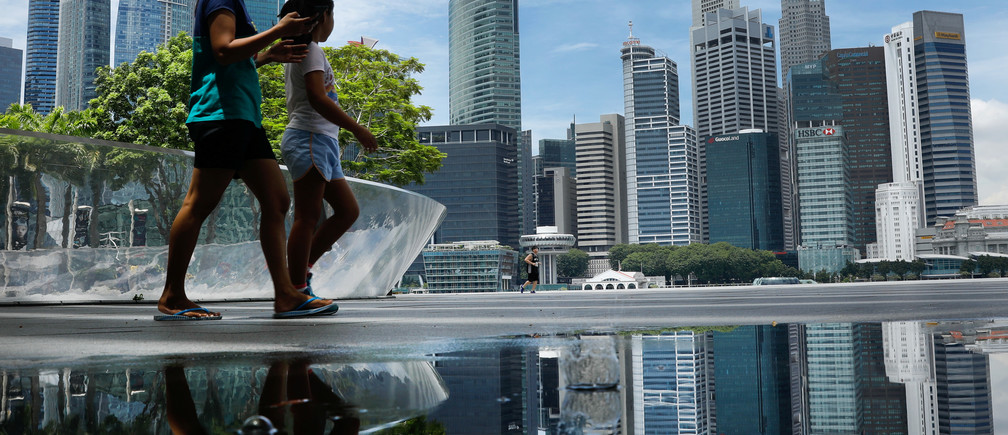 People pass the skyline of Singapore October 11, 2017. REUTERS/Edgar Su - RC19D146ABD0