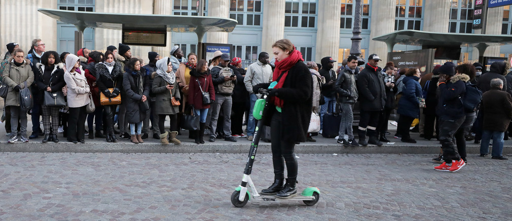 A woman rides a scooter past the people waiting on bus stops at Gare du Nord station during a strike by all unions of the Paris transport network (RATP) and French SNCF workers in Paris as part of a second day of national strike and protests in France, December 10, 2019.