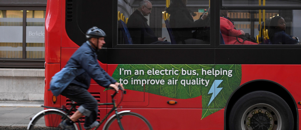 A cyclist rides past an electric public bus in London