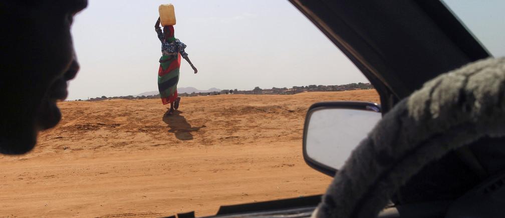 A woman carries water in Abu Shock IDPs camp in Al Fashir, capital of North Darfur, Sudan, September 6, 2016. REUTERS/Mohamed Nureldin Abdallah - RTX2OCMZ