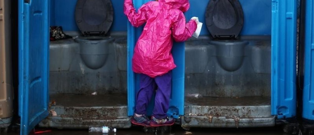 A migrant girl, part of a caravan of thousands from Central America trying to reach the United States, tries to avoid flooded ground by holding on to the door of a toilet after heavy rainfall in a temporary shelter in Tijuana, Mexico, November 29, 2018. REUTERS/Hannah McKay - RC16C4C99E40