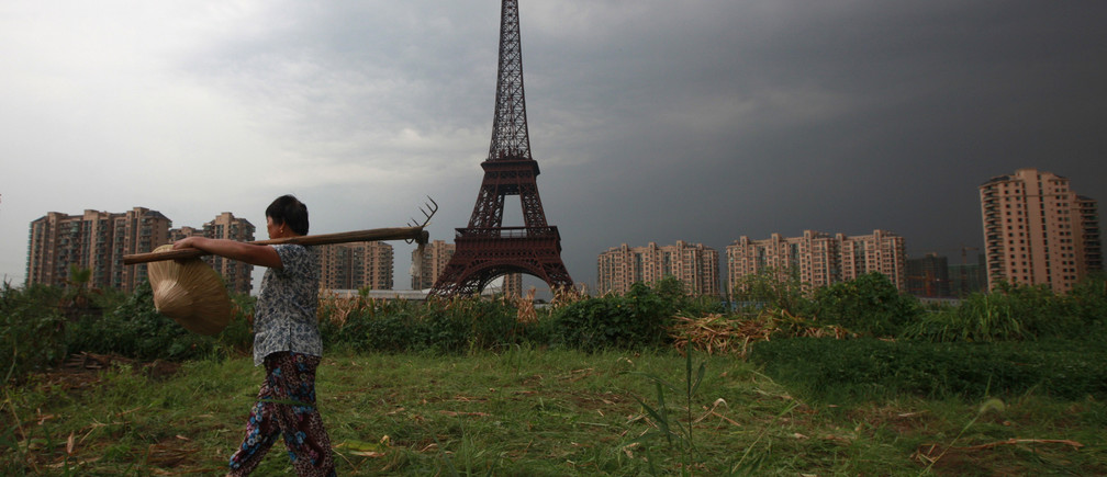 "A farmer carrying a rake walks down a dirt road past a replica of the Eiffel Tower at the Tianducheng development in Hangzhou, Zhejiang Province August 1, 2013. Tianducheng, developed by Zhejiang Guangsha Co. Ltd., started construction in 2007 and was known as a knockoff of Paris with a scaled replica of the Eiffel Tower standing at 108 metres (354 ft) and Parisian houses. Although designed to accommodate at least 10 thousand people, Tianducheng remains sparsely populated and is now considered as a ""ghost town"", according to local media. REUTERS/Aly Song (CHINA - Tags: SOCIETY BUSINESS REAL ESTATE AGRICULTURE TPX IMAGES OF THE DAY) - RTX127WU"