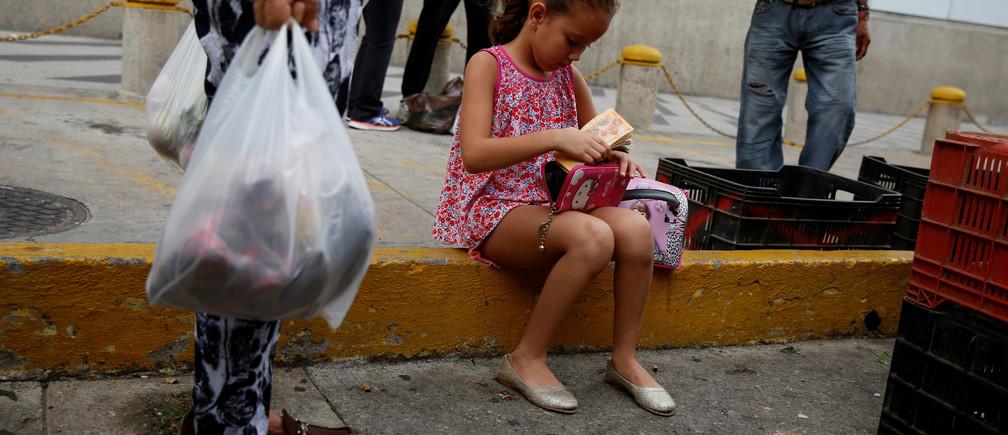 A girl puts Venezuelan bolivar notes into her purse at a street market in Caracas, Venezuela August 13, 2016. REUTERS/Carlos Garcia Rawlins - RTX2KJPT