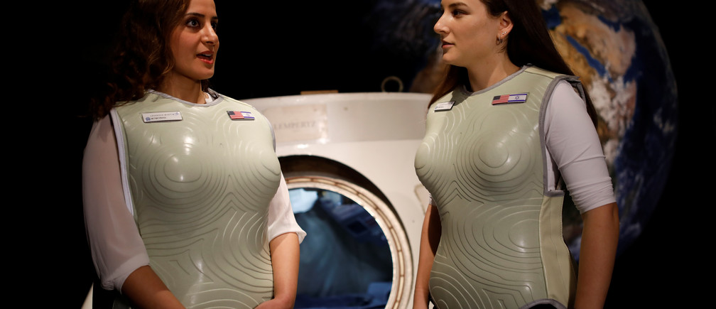 Women wearing prototypes of Stemrad's new protective vest, Astrorad, stand near Russian spacecraft, Excalibur-Almaz Space Capsule, during a demonstration for Reuters, at Madatech, National Museum of Science Technology and Space in Haifa, Israel February 23, 2017. Picture taken February 23, 2017. REUTERS/Amir Cohen - RTS119FE