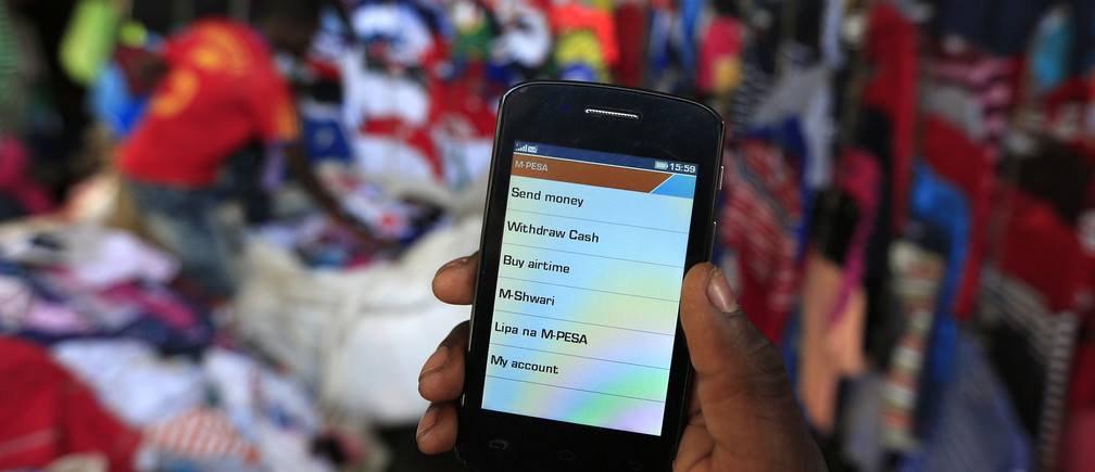 A man prepares to make an M-Pesa payment at an open-air market in Kibera, Nairobi.
