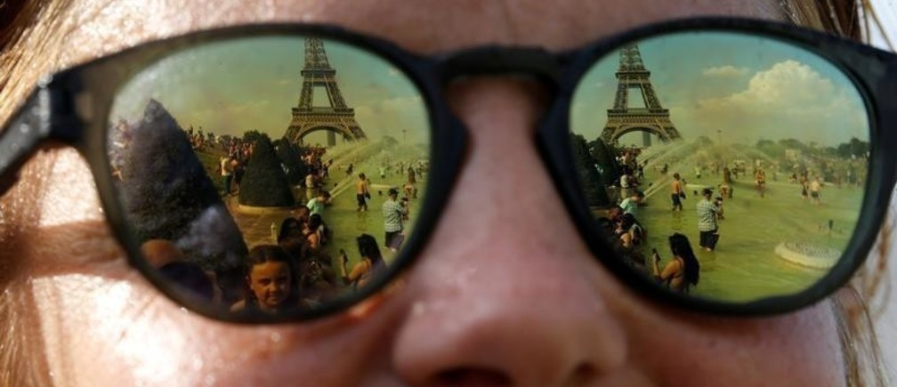People cooling off in the Trocadero fountains across from the Eiffel Tower are reflected in sunglasses in Paris as a new heatwave broke temperature records in France, July 25, 2019. REUTERS/Pascal Rossignol     TPX IMAGES OF THE DAY - RC1899436500