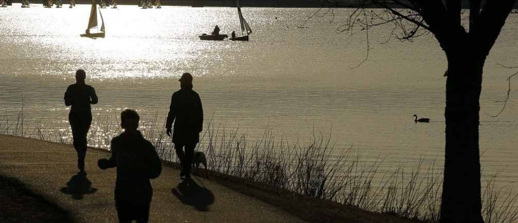 Joggers run past sailboats on the Charles River on an early spring evening in Boston, Massachusetts April 3, 2014.