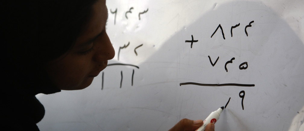 A woman takes part in a math class at the Family Guidance Center women's shelter in Kabul, August 9, 2009.  According to a 2006 report by the UK-based NGO 'Womankind,' anywhere between sixty and eighty percent of marriages in Afghanistan are forced, 57 percent of brides are under the age of 16, and 87 percent complain of domestic violence.  Afghan women suffer from the lowest literacy rate in the world, at 13 percent.   REUTERS/Lucy Nicholson (AFGHANISTAN SOCIETY EDUCATION) - GM1E5891MAI01