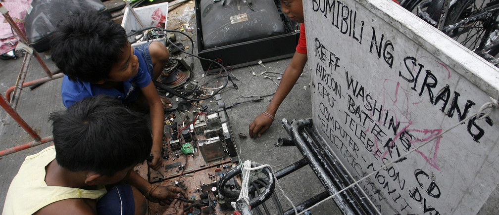 Children recover copper and other metals from discarded televisions and other electronic waste, which they exchange for money from nearby junkshops, along a road in Manila April 7, 2011. An e-waste recycling and reclamation company salvages gold and other precious metals like silver, copper and palladium from microprocessors of discarded electronic products like desktop computers, laptops, mobile phones and copying machines. About 4000 integrated circuits from discarded mobile phones can produce about 100 grams of gold.  REUTERS/Cheryl Ravelo (PHILIPPINES - Tags: SOCIETY EMPLOYMENT BUSINESS ENVIRONMENT) - GM1E7480PWO01