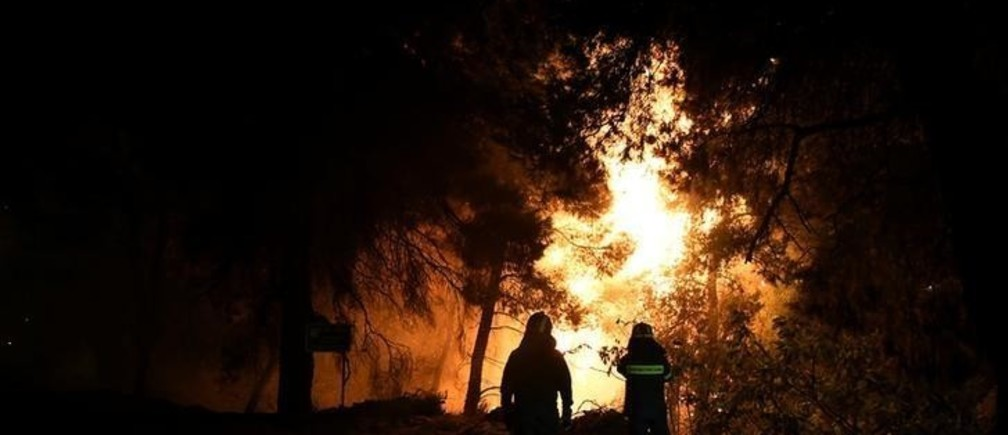 Firefighters looks at rising flames during a wildfire near the village of Psahna, in Evia, Greece, August 12, 2018. Picture taken August 12, 2018. REUTERS/Michalis Karagiannis