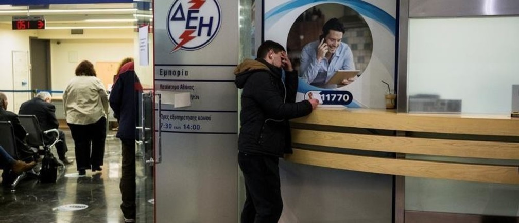 A man waits at a Public Power Corporation (PPC) branch to enter a repayment scheme for their debts in Athens, Greece, March 3, 2017. Picture taken March 3, 2017.