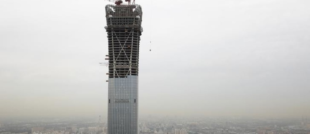 Cranes stand atop the China Zun skyscraper that is under construction in the Central Business District of Beijing, China August 26, 2017. REUTERS/Thomas Peter