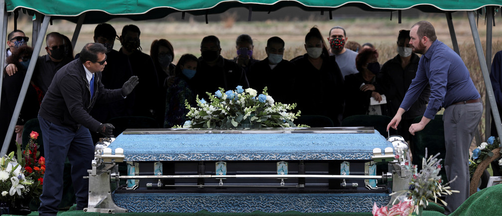 Family members of JBS USA meat packing plant employee Saul Sanchez watch as his casket is lowered during his funeral after he died of coronavirus disease (COVID-19) in Greeley, Colorado, U.S., April 15, 2020. REUTERS/Jim Urquhart - RC2C5G9UP3JL