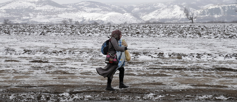 A migrant walks through a frozen field after crossing the border from Macedonia, near the village of Miratovac, Serbia, January 18, 2016.