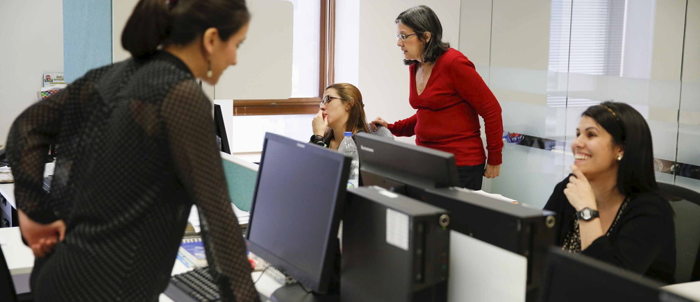Employees of multinational headhunter Korn/Ferry work at the headquarters office of the company in Caracas August 3, 2015. Headhunters across Latin America are tapping Venezuela for low-cost professionals as a deepening economic crisis has left many skilled workers earning less money than taxi drivers and waiters. Highly-trained Venezuelans are seeking to escape a decaying socialist economy in which they often have to work second jobs and spend hours in line to buy basic goods such as milk or diapers. Picture taken on August 3, 2015. REUTERS/Carlos Garcia Rawlins - RTX1N6MC