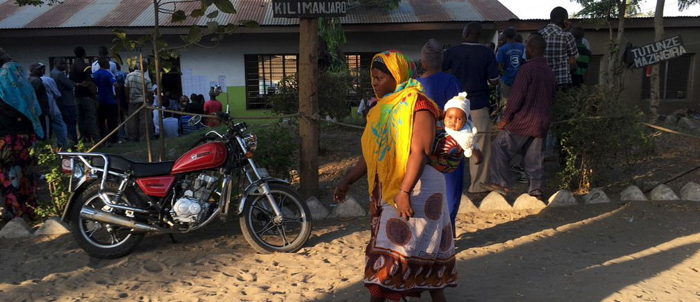 A woman carries her child as she arrives at a polling station before the opening of the voting process during the presidential and parliamentary election in Temeke district of Dar es Salaam, October 25, 2015. Tanzanians voted on Sunday in presidential and parliamentary polls in which the ruling party is expected to fend off rivals led by former Prime Minister Edward Lowassa, who has tapped into mounting anger over corruption and the slow pace of change. REUTERS/Drazen Jorgic - GF20000031743
