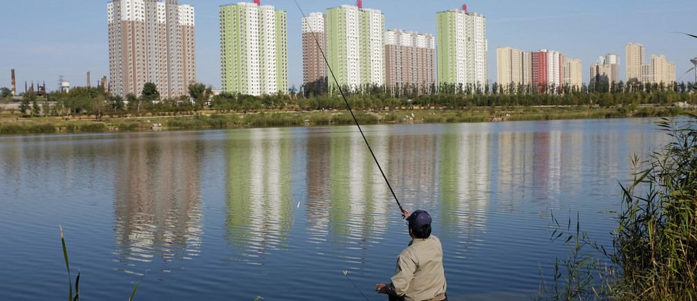 A resident fishes at a lake near apartment blocks in Beijing October 20, 2013. Average new home prices in China's 70 major cities in September rose 9.1 percent from a year earlier, according to Reuters calculations based on official data published on Tuesday, marking the ninth straight month of year-on-year increases. Picture taken October 20, 2013. REUTERS/Jason Lee (CHINA - Tags: BUSINESS REAL ESTATE TPX IMAGES OF THE DAY) - RTX14J4V