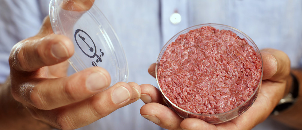 Professor Mark Post holds the world's first lab-grown beef burger during a launch event in west London, August 2013.