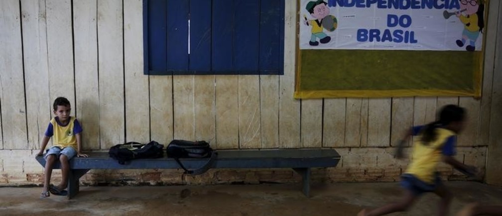 """A boy sits as other children run in the corridors of their school in the village of Rio Pardo next to Bom Futuro National Forest, in the district of Porto Velho, Rondonia State, Brazil, August 31, 2015. The banner reads """"Independence of Brazil"""". The town of Rio Pardo, a settlement of about 4,000 people in the Amazon rainforest, rises where only jungle stood less than a quarter of a century ago. Loggers first cleared the forest followed by ranchers and farmers, then small merchants and prospectors. Brazil's government has stated a goal of eliminating illegal deforestation, but enforcing the law in remote corners like Rio Pardo is far from easy. REUTERS/Nacho Doce  PICTURE 22 OF 40 FOR WIDER IMAGE STORY """"EARTHPRINTS: RIO PARDO"""" SEARCH""""EARTHPRINTS PARDO"""" FOR ALL IMAGES   - GF20000046417"""