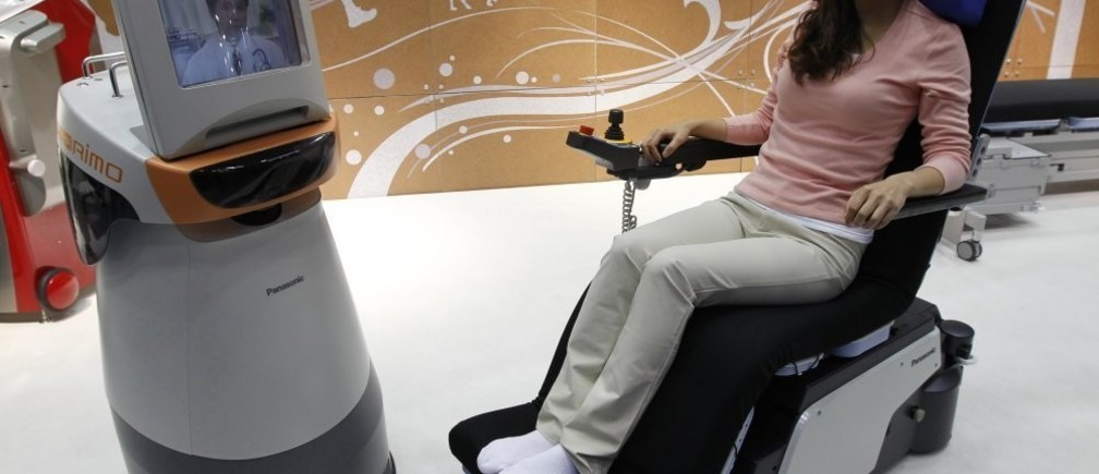 A demonstrator sits in an electronic wheelchair as she talks with a doctor, seen on the monitor of Panasonic's HOSPI-Rimo, at its presentation in Tokyo October 4, 2011. The communications assistant robot, which has automatic movement and visual communication functions, enable conversations between people who are in separate places, such as when a doctor is in hospital and a patient at home. According to Panasonic, the robot can help people with limited mobility. REUTERS/Kim Kyung-Hoon (JAPAN - Tags: SCIENCE TECHNOLOGY SOCIETY BUSINESS HEALTH)