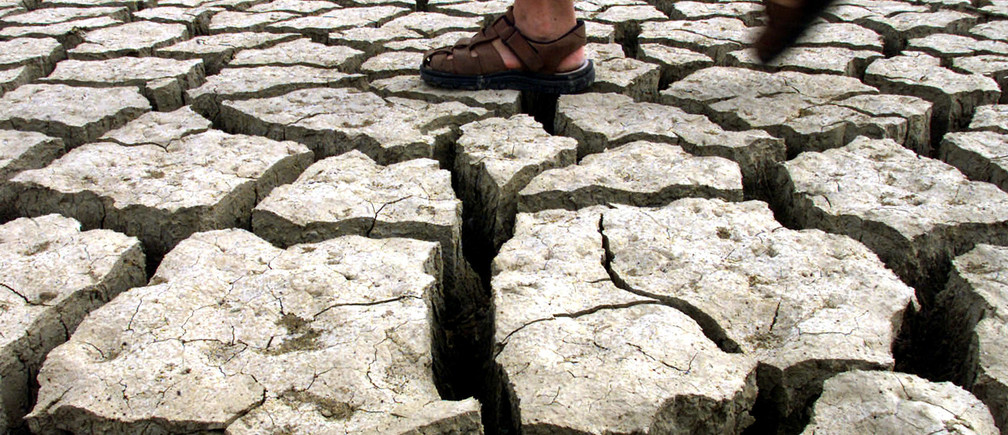 A man walks in the dried-out lake of Jato near the Sicilian village of Partinico July 15, 2002. The Italian government prepared on Sunday to send in the army to help combat a drought that has withered crops, damaged industry and provoked fury in the southern half the country. With a state of emergency declared in four regions, ministers promised at the weekend to throw everything they had at the mounting problem which has been caused by a mix of unusually dry weather and poor water management. NO RIGHTS CLEARANCES OR PERMISSIONS ARE REQUIRED FOR THIS IMAGE NTRES REUTERS/Tony Gentile  PC/CRB - RP3DRHXPBCAB