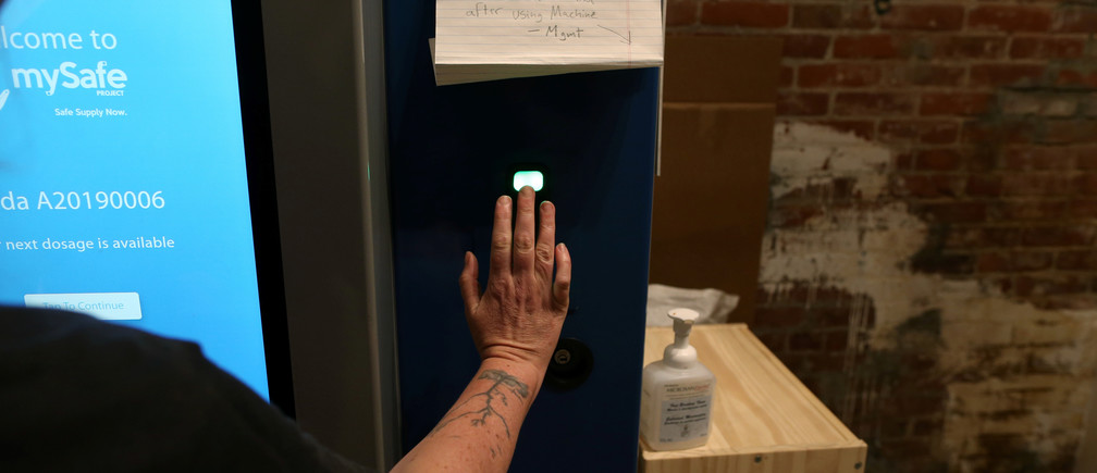 "A woman demonstrates how the mySafe narcotic dispensing machine uses a palm-print ID at the Overdose Prevention Society as the local health unit has begun prescribing a ""safe supply"" of narcotic alternatives to combat overdoses due to poisonous additives and to entice addicts and homeless into practicing social distancing to help slow the spread of coronavirus disease (COVID-19) in the Downtown Eastside of Vancouver, British Columbia, Canada April 7, 2020. Picture taken April 7, 2020. REUTERS/Jesse Winter - RC2S5G9CUXGD"
