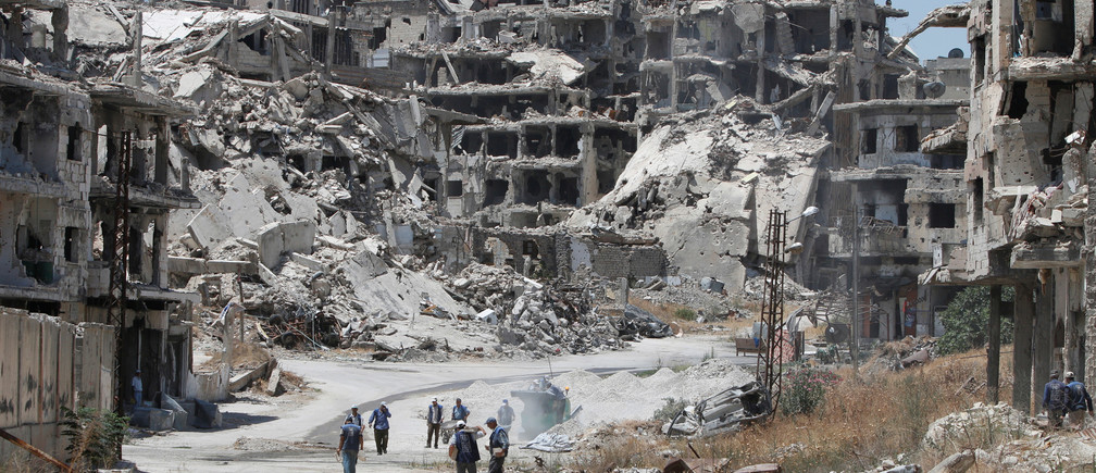 Workers collect the rubble of damaged buildings to be recycled and reused for reconstruction, under the supervision of the United Nations Development Programme (UNDP) in Homs, Syria.