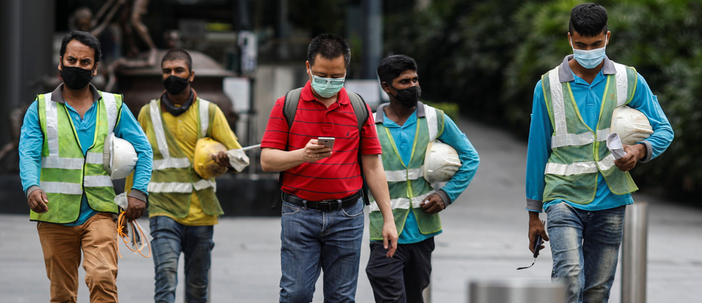 Migrant workers in essential services wearing safety vests cross a street at Orchard Road, amid the coronavirus disease (COVID-19) outbreak in Singapore, May 27, 2020. REUTERS/Edgar Su - RC2TWG9L17PT