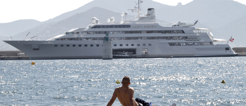A man enjoys the sunny weather as he looks at the Lady Moura Yacht during the 63rd Cannes Film Festival May 17, 2010.    REUTERS/Eric Gaillard (FRANCE - Tags: SOCIETY ENVIRONMENT) - GM1E65H1T2201