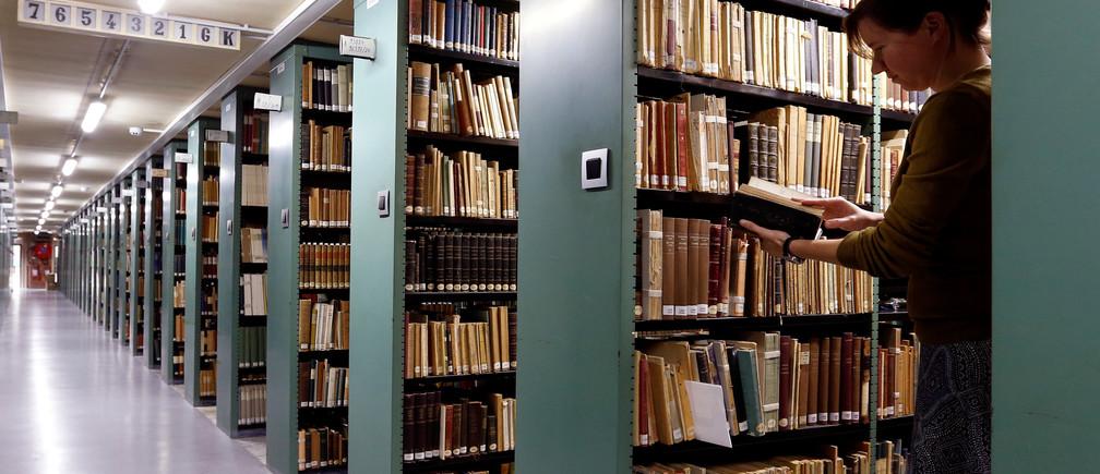 "A woman consults a book in the library of the university KU Leuven ""Katholieke Universiteit Leuven"" in Leuven, Belgium, June 8, 2016. REUTERS/Francois Lenoir/File Photo - S1AETJUWUDAC"